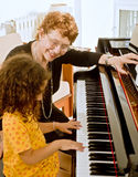 The piano teacher. Senior piano teacher with young girl student stock photos