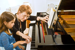 The piano teacher. Senior piano teacher with young girl student royalty free stock photos