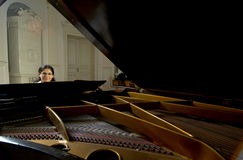 Piano Teacher Across Baby Grand. Portrait of a female piano teacher looking downward as she plays grand piano.  Taken from distance across open piano top Stock Image