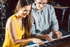 Piano teacher giving music lessons to his student. Piano teacher giving lessons to his student in music school stock photos