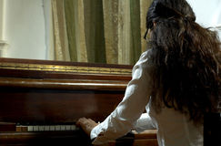 Piano Teacher Hands On Keys. Portrait of a female piano teacher looking downward as she plays piano.  Shot from back left view Stock Image