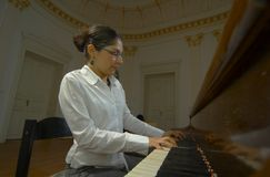 Piano Teacher Playing From Keyboard Viewpoint. Portrait of a female piano teacher looking downward as she plays piano.  Shot from right side view, near piano Stock Images