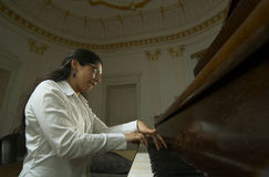 Piano Teacher Playing Low Viewpoint. Portrait of a female piano teacher looking downward as she plays piano.  Shot from right side view, from low viewpoint near Royalty Free Stock Images
