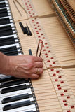 Piano tuning 3. Detailed view of Upright Piano during tuning.A technician using a Tuning fork to adjust the piano. Please see my other photos of a piano being royalty free stock photography