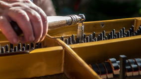 Piano tuning. Tuning a grand piano by experienced hand Royalty Free Stock Photography