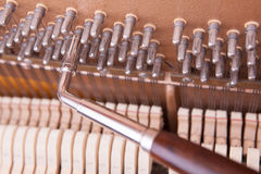 Piano. Tuning key on a pin of upright piano. The process of tunning Stock Photo