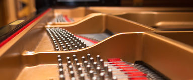 Piano tuning pins. Concert piano pin block with tuning pins and stress bars, selective focus stock photography