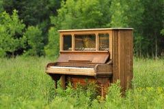 Piano vertical viejo abandonado en un campo verde Imagen de archivo libre de regalías