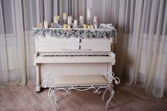 Piano viejo con las decoraciones del Año Nuevo, velas Imágenes de archivo libres de regalías