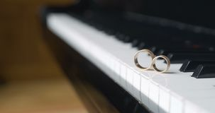 Piano and wedding rings. Close up shoot of wedding rings on white piano keyboard. Wedding engagement love background stock video