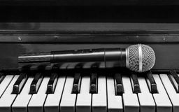 Piano and wireless microphone. Black and white pianos and wireless microphone Stock Photos