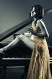 Piano woman. Sexy woman with a glass of whine near a piano Stock Images