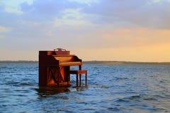 Piano y taburete de piano que se pega fuera del lago Imagenes de archivo
