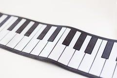 Pianodetaljskott på en vit tabell Fotografering för Bildbyråer