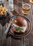 Pianohamburgare med bacon och kotletten med ost, tomat, gräsplaner arkivbild