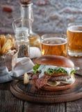 Pianohamburgare med bacon och kotletten med ost, tomat, gräsplaner arkivfoto