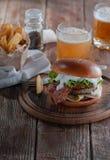 Pianohamburgare med bacon och kotletten med ost, tomat, gräsplaner royaltyfria bilder