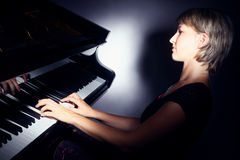 Pianopianistspelare med flygeln royaltyfria bilder