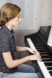 Pianos. Young, pretty girl playing the piano Royalty Free Stock Photo
