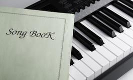 Pianosleutels en liedboek Stock Foto's