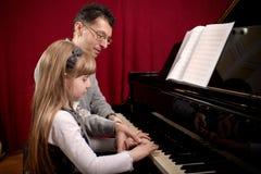 Pianospelare och hans liten flickastudent under kurs Royaltyfri Foto