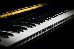 Pianotangenter av ett klassiskt piano i mörkret arkivfoto