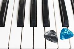 Pianotangenter och gitarrhackor arkivbild