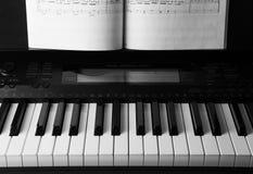 Pianotangenter och musikalisk bok Arkivfoto