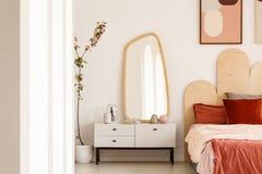 Pianta accanto alla tavola di condimento bianca con lo specchio in camera da letto rossa dentro Immagine Stock