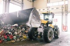 Pianta automatizzata capannone per la separazione dei rifiuti domestici Un escavatore con un secchio alzato raccoglie e trasporta fotografia stock