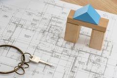 Pianta della casa con il modello del blocchetto di legno del giocattolo e una chiave con l'anello d'annata immagini stock libere da diritti