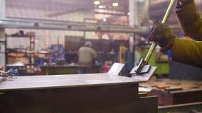 Pianta della costruzione Un lavoratore che piega un dettaglio riscaldato del ferro con un supporto speciale video d archivio