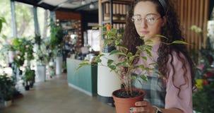 Pianta di innaffiatoio sveglia della giovane donna dallo spruzzatore che funziona nel deposito di fiore stock footage