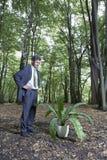 Pianta di Looking At Potted dell'uomo d'affari in foresta fotografie stock libere da diritti