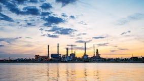 Pianta laterale di industria della raffineria di petrolio del fiume lungo la mattina crepuscolare Fotografia Stock