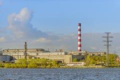 Pianta metallurgica vicino allo stagno su un fondo di cielo blu Fotografia Stock