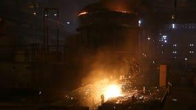 Pianta per la produzione di acciaio Un forno di fusione elettrico L'operaio preleva un campione per metallo stock footage