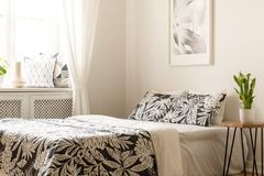 Pianta sulla tavola accanto al letto con gli strati modellati in bedro luminoso Fotografia Stock