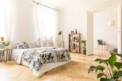 Pianta sulla tavola accanto al letto con gli strati modellati in bedroo bianco Immagine Stock Libera da Diritti