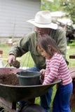 Piantatura dei fiori con il Grandpa Fotografia Stock