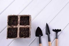 Piantatura i vasi e dei pochi strumenti di giardino fotografia stock libera da diritti