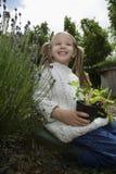 Piante della tenuta della ragazza in giardino immagine stock libera da diritti
