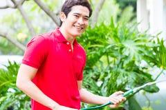 Piante di innaffiatura asiatiche dell'uomo con il tubo flessibile di giardino Fotografie Stock Libere da Diritti
