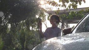 Piante di innaffiatura asiatiche della ragazza in giardino con il tubo flessibile stock footage