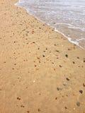 Piasek na plaży pełno seashells, kamienie, otoczak z fala c Zdjęcia Royalty Free