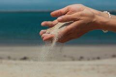 Piasek nalewa przez palców przeciw morzu Natura Obrazy Royalty Free