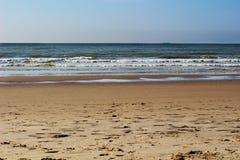 Piasek plaża z przybywającymi fala i biel pienimy się na a Zdjęcia Royalty Free
