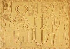 Piaska koloru tynku barelief z bóg Antyczny Egipt słońce bóg akademie królewskie bóg Horus i dwa bogini, obrazy stock
