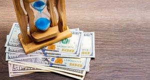 Piaska zegar jest wartym dolarowych rachunki Piaska Dollars_ i zegar obrazy stock