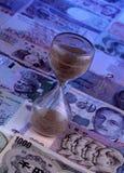 Piaska zegar na obcych walut notatkach Fotografia Stock